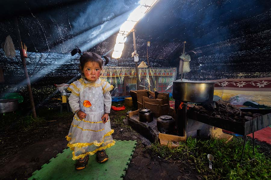Nomad Tibetan kid inside her tent. Grasslands around Zorge.
