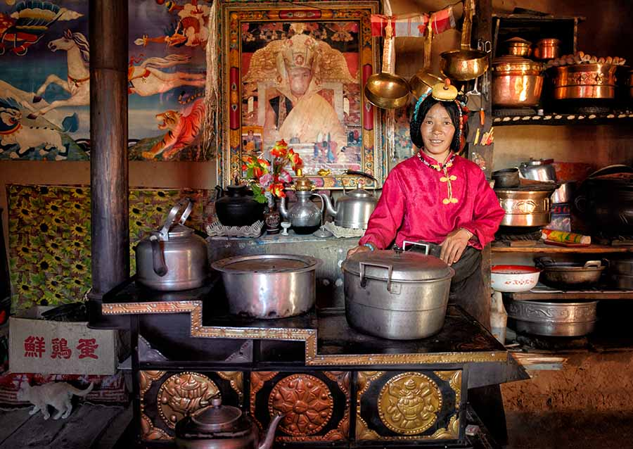 Tibetan woman in her golden kitchen.  Tibetan plateau