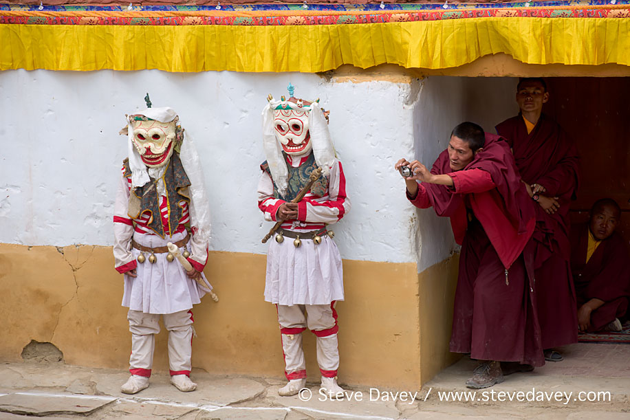 Masked Cham Dancers being photographed by a Buddhist monk, Korzo