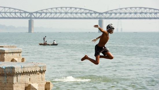 Varanasi, India: A boy jumps into the Ganges River for his bath