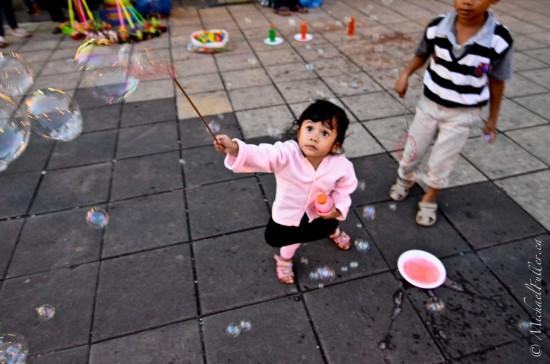 "These adorable kids playing in Bukittinggi's ""Jam Gadang"" (clock tower) square."